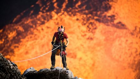An extraordinary shot of Chris abseiling into a live volcano