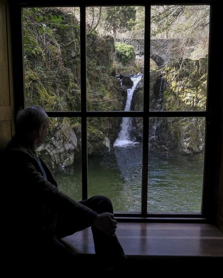 An elderly visitor takes a rest atThe Grot near Rydal Mount