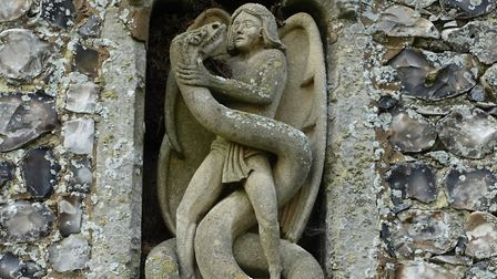 Heroic: St Michael himself battles with a serpent in this modern sculpture in the porch niche at Irs
