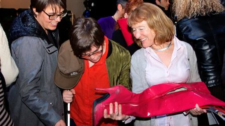 """With Anne's help, a blind audience member enjoys discovering props on a theatre """"touch tour"""""""