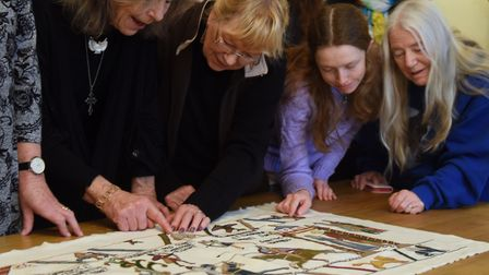 Volunteers study the first panel of the modern Bayeux-style tapestry being made in Norfolk (photo: D