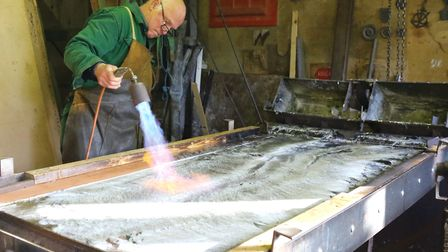 Hot metal - Brian Turner with sheets of molten lead. Photo: Serena Shores