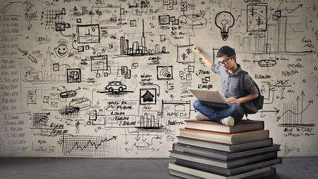 Young Asian boy with nerdy black glasses sitting on a book hill, drawing his ideas creatively on the