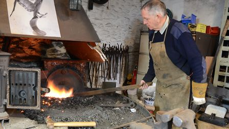 Fused metal sculptor Nigel Wells at work in the Old Forge