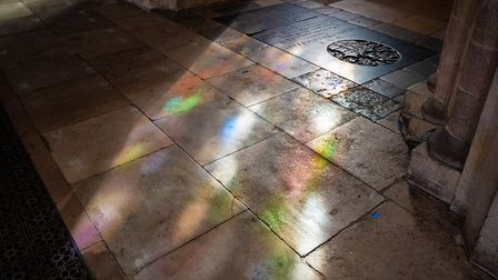 The sun streaming though stained glass creates a spill of colour on the flagstones. Photo: Bill Smit