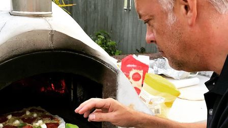 Mark Fitch adds a flourish to his home-baked pizza. Photo: Mark Fitch