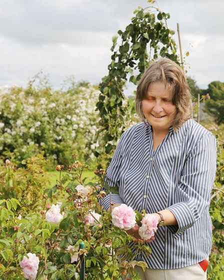 Catherine admiring one of the roses is the gardens she developed at Dutton Hall in the Ribble Valley