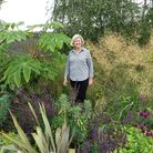 Julianne Fernandez in one of her deep borders flanked by exotic Tetrapanax papyrifer , the rice-pape