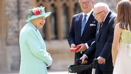 Queen Elizabeth II talks Captain Sir Thomas Moore and his family after awarding his knighthood durin