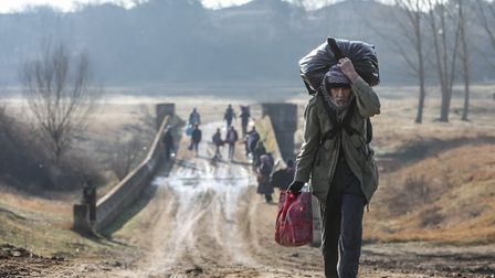 Refugees and migrants walk as they attempt to enter Greece from Turkey by crossing the Evros river o