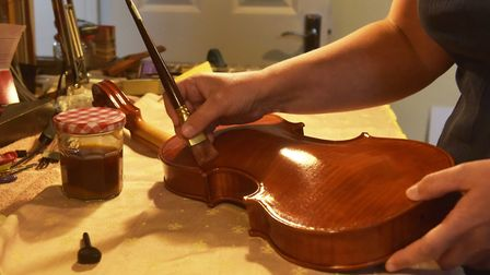 Dota carefully applies varnish to an instrument. Photo: Brittany Woodman