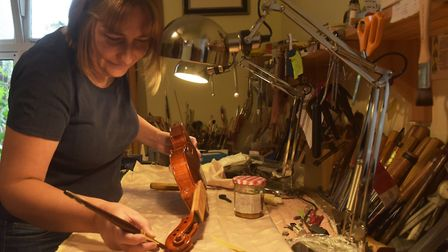 Dota works on the scroll of a violin in her workshop. Photo: Brittany Woodman