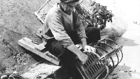 Sheringham fisherman R. H. West repairs his crab pot on the seafront at Sheringham, May 195. Photo: