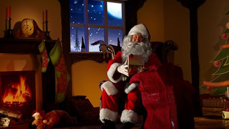 Santa holding a bag full ofchristmas gifts. He is sitting in his animated grotto. Horizontal image.