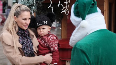 Leo posts his letter to Sanata with help from one of the Elves at the Arc in Bury St Edmund. Photo: