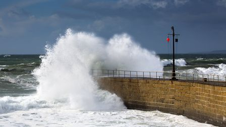 A wave breaks against the end of the pier
