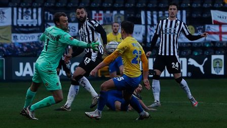 Notts County keeper Sam Slocombe gets a hand to a ball as Torquay United player Billy Waters closes