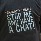 A community builder's back in a jacket that has the words 'Stop Me and Have A Chat' written on it