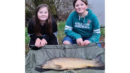 Summer Skelly and Evie Stewart with a mid double figure common carp from Newbarn
