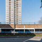 An empty car park with a block of flats in the background