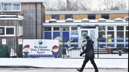 A woman walks past a social distance sign which is displayed outside a shut down primary schoolin Newcastle-under-Lyme