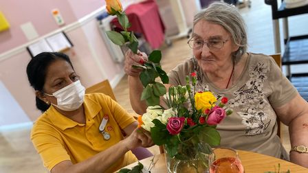 Joan Lyne puts together an arrangement with a Mornington Hall Care Home staff member.