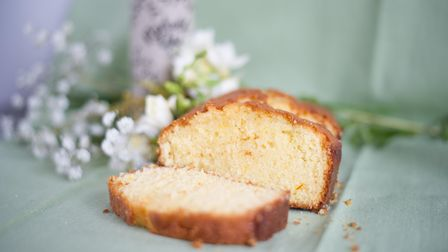 Gin, lemon and saffron loaf cake on a platter with white spring flowers