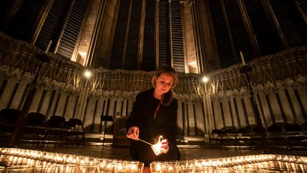 York Minster employee Leanne Woodhurst helps light six hundred candles in the shape of the Star of D