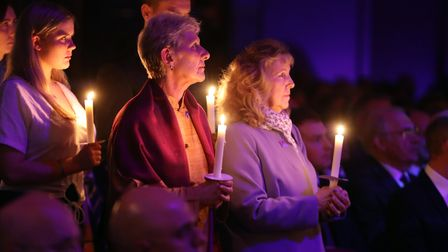 People hold candles during the UK Holocaust Memorial Day Commemorative Ceremony at Central Hall in W