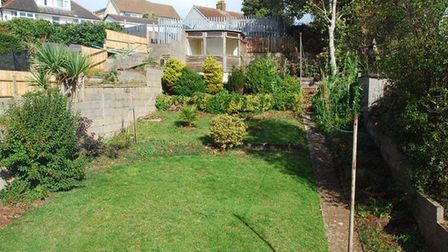 Therear garden featuresasloping lawn and path with a border bed to the top level which is paved and has a summer house...