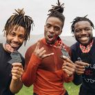 Three runners pose with medals.