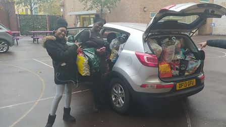 Two students help pack a car full of food supplies.