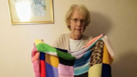 Timebankers knit squares for the homeless, and Dorothy sews them together.