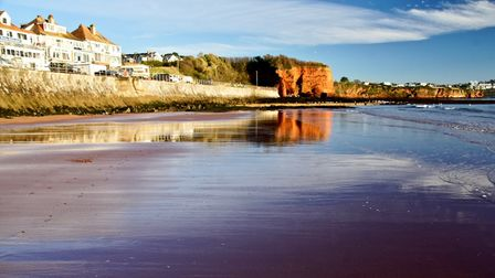 Preston beach from a different angle, with red cliffs meeting calm sea