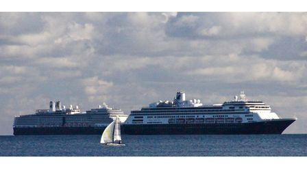 A small yacht sails past two of the huge cruise ships in Torbay