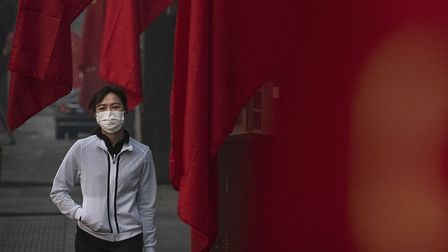 A woman wears a protective mask as she walks by Chinese flags in a street during the Chinese New Yea