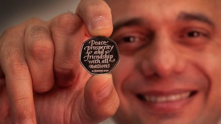 Former chancellor Sajid Javid holding the Brexit coin, a 50p bearing the inscription 'Peace, prosper