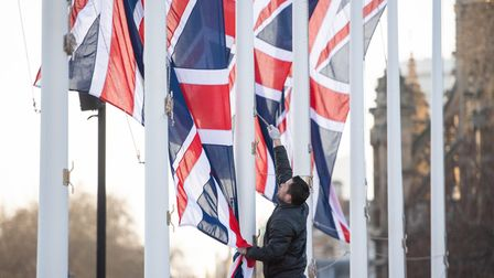 A worker removes Union flags from flagpoles in Parliament Square, London