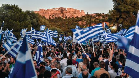 Supporters of Greece's opposition party New Democracy wave Greek flags and wait for the speech of th
