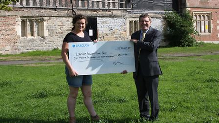 Carrie Horwood presents a cheque to the chairman of The Llanthony Secunda Priory Trust, Jeremy Willi