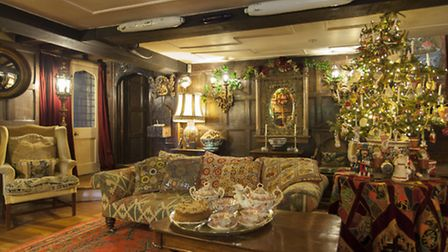 The sofa in the hall is upholstered with a kelim rug and the red carpet is Turkish dating from the 1