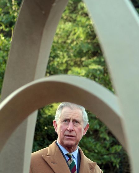 Prince Charles looks at the new sculpture in the hospice's garden by artist Jim Milne