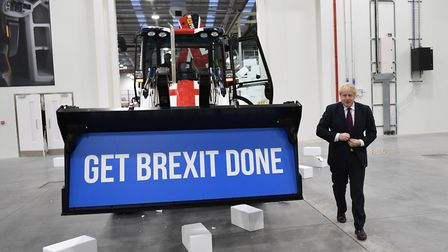 "Prime Minister Boris Johnson walks away after driving a union flag-themed JCB, with the words ""Get B"
