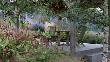 A raised deck is set amongst waves of perennial planting