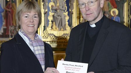 The Very Reverend Michael Tavinor, Dean of Hereford presents the donation to Mrs Sarah Sharp-Smith,