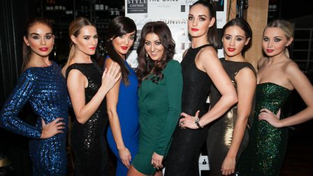 Designer Nadine Merabi with models in her glamorous evening wear creations