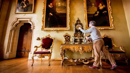 Conservation Manager Peter Nottingham winding a clock dating from 1690 in the Drawing Room. There ar