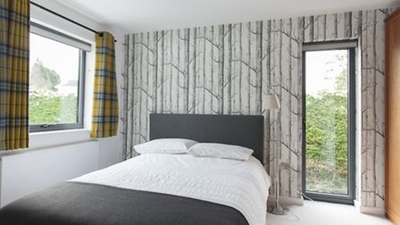The guest bedroom has 'Forest' wallpaper by Cole & Son, and the bright Lomond check curtain fabric i