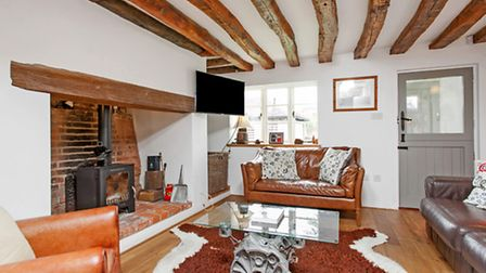 The sitting room is a mix of country and contemporary with inglenook fireplace, woodburning stove an
