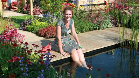 Keeping cool...Pip Probert of Bromborough in her garden 'The Narrows' reflecting the shape of a typi